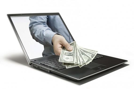 Рука с деньгами из монитора компьютера