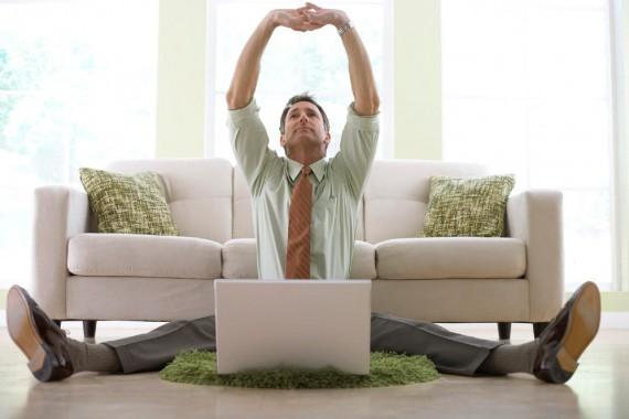 Мужчина сидит на полу перед ноутбуком и потягивается